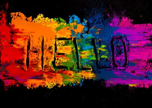 Testo scritto a mano ciao sul colore di polvere colorata holi su sfondo nero Foto Gratuite