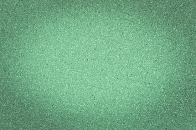 Texture di colore verde granito con piccoli punti, con vignettatura, utilizzare lo sfondo. Foto Premium