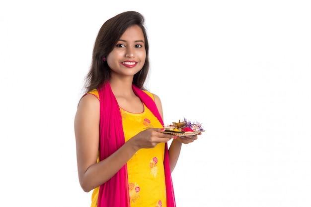 Thali indiano bello di pooja della tenuta della ragazza o culto di esecuzione su bianco Foto Premium