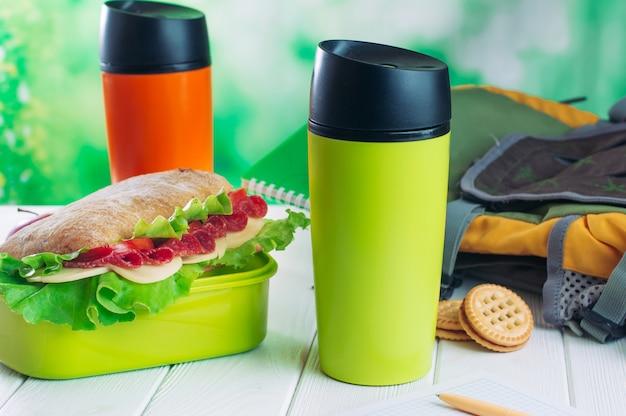 Thermos tazze vicino a scatola di pranzo e zaino sul tavolo di legno Foto Premium