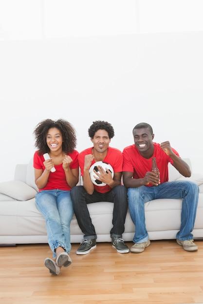 Tifosi che si siedono sul divano che incoraggiano insieme a casa nel salone Foto Premium
