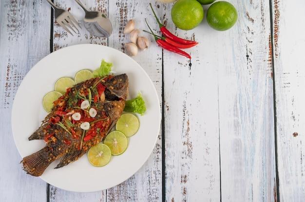 Tilapia fritto con salsa di peperoncino, insalata di limone e aglio su un piatto su un fondo di legno bianco Foto Gratuite