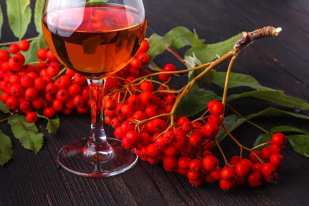 Tintura di sorbo di alcool in vetro, concetto di alcol fatto a mano Foto Premium
