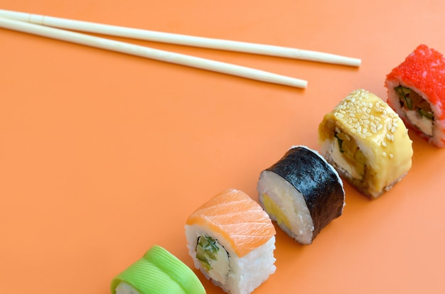 Tipi differenti di rotoli di sushi asiatici su fondo arancio. vista dall'alto di minimalismo piatto con cibo giapponese Foto Premium