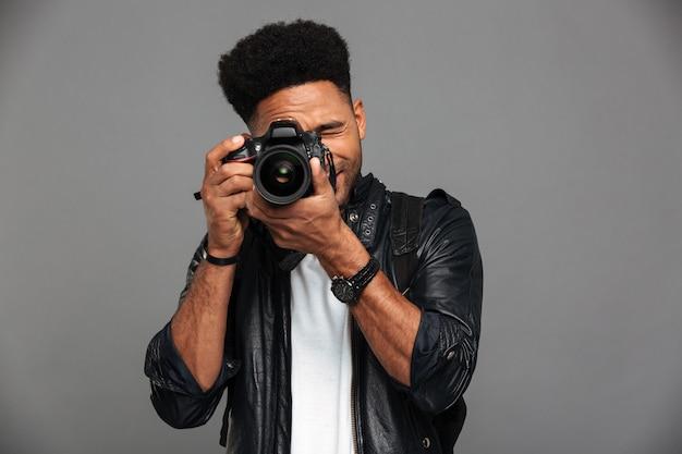 Tipo africano bello con taglio di capelli alla moda che prende foto sulla macchina fotografica digitale Foto Gratuite