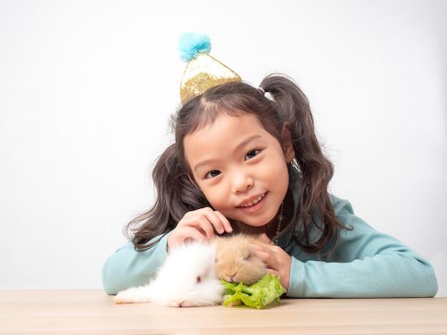 Tipo piccola ragazza carina e conigli bianchi e marroni del bambino sulla tavola di legno. Foto Premium