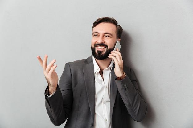 Tipo positivo positivo nel chiacchierare mobile di usura convenzionale che gesturing mentre per mezzo del telefono cellulare, isolato sopra grey Foto Gratuite