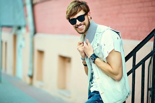 Tirante bello sorridente divertente dell'uomo bello dei pantaloni a vita bassa in panno alla moda di estate nella via in occhiali da sole Foto Gratuite