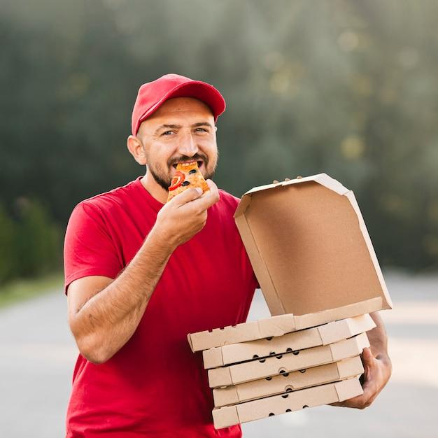 Tirante medio che mangia pizza Foto Gratuite