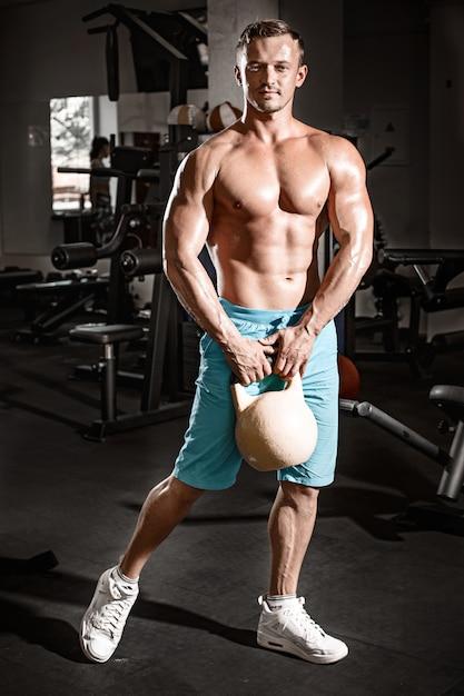Tirante muscolare del bodybuilder che fa le esercitazioni con peso in ginnastica Foto Gratuite
