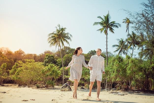 Tiri le coppie in secco che camminano sul romanticismo romantico di vacanze estive di vacanza di luna di miele di viaggio. giovani amanti, donna e uomo felici che si tengono per mano abbracciando all'aperto. foresta tropicale sullo sfondo Foto Premium
