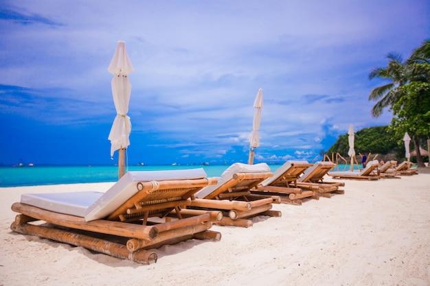 Tiri le sedie in legno in secco per le vacanze sulla spiaggia tropicale Foto Premium