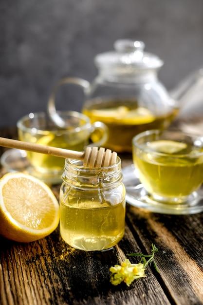 Tisana al limone e miele in tazza di vetro e teiera Foto Premium