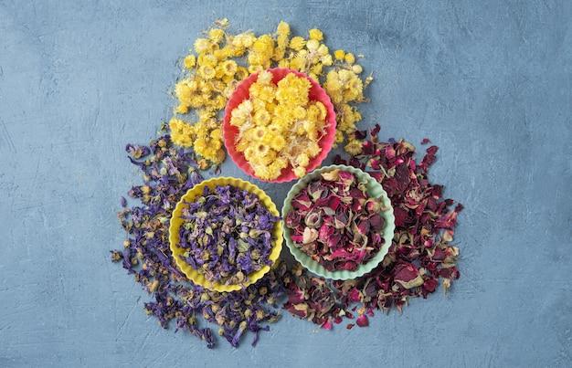 Tisana aromatica alla camomilla, rosa e lavanda sfusa sul tavolo di legno blu Foto Premium