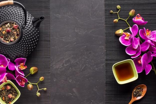 Tisana con l'ingrediente essiccato e fiore di orchidea su tovaglietta nera Foto Gratuite