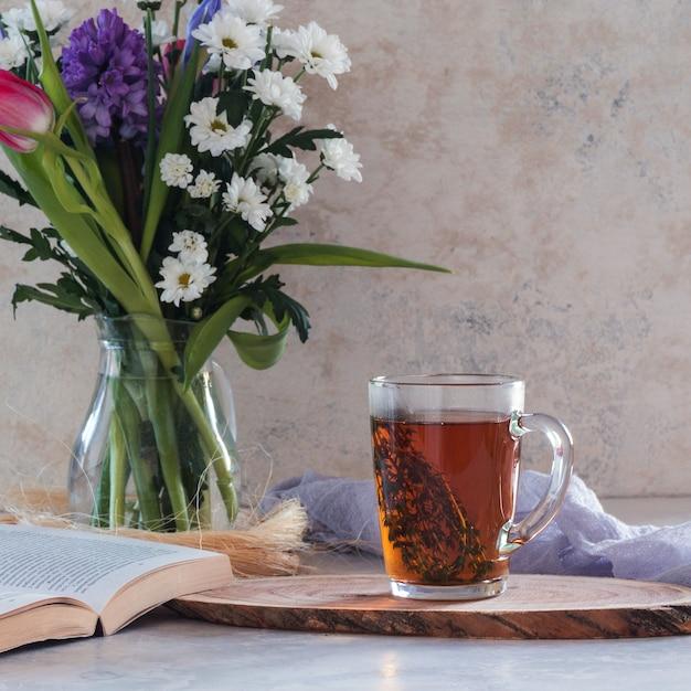 Tisana con timo su bianco con bouquet di fiori e libro Foto Premium