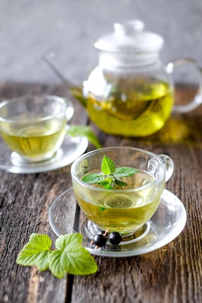 Tisana verde con bacche in tazza di vetro sulla tavola di legno Foto Premium