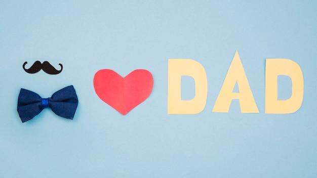 Titolo di cuore e papà rosso vicino a farfallino e baffi Foto Gratuite
