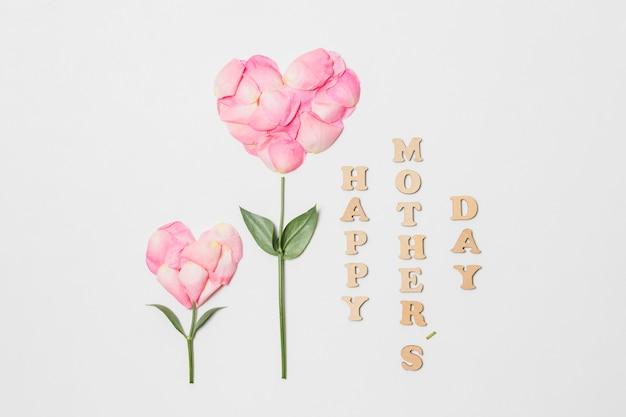 Titolo di giorno di madri felice vicino alla fioritura rosa a forma di cuore Foto Gratuite