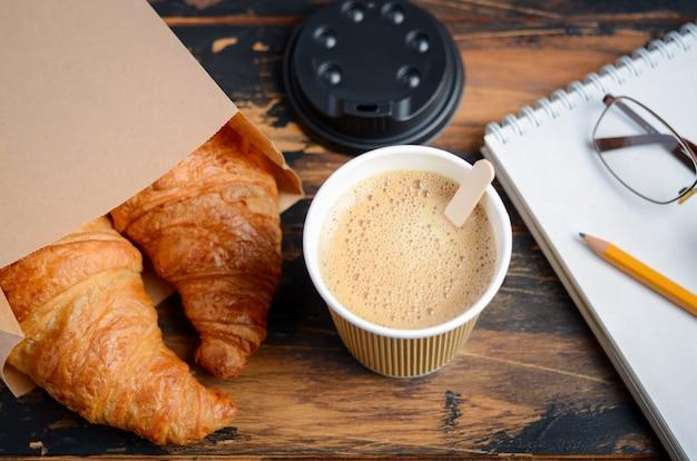 Togliere la tazza di caffè con cornetto sul tavolo di legno. Foto Premium