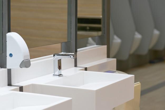 Toilette per lavare la mano con goccia di sapone su sfocatura sfondo orinatoio Foto Premium