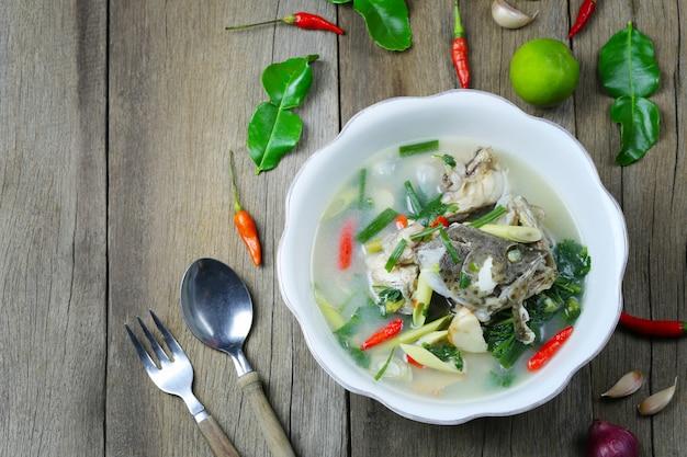 Tom yum grouper fish spicy soup di cibo tailandese in una ciotola sul pavimento di legno. Foto Premium