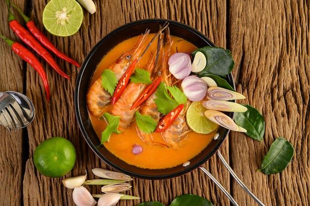 Tom yum kung thai piccante zuppa di gamberi con citronella, limone, galanga e peperoncino sul tavolo di legno, cibo in thailandia Foto Gratuite