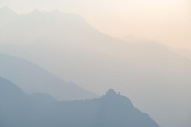 Tonalità blu distante catena montuosa delle alpi con il profilo dell'abbazia di st. michel nella parte inferiore. Foto Premium