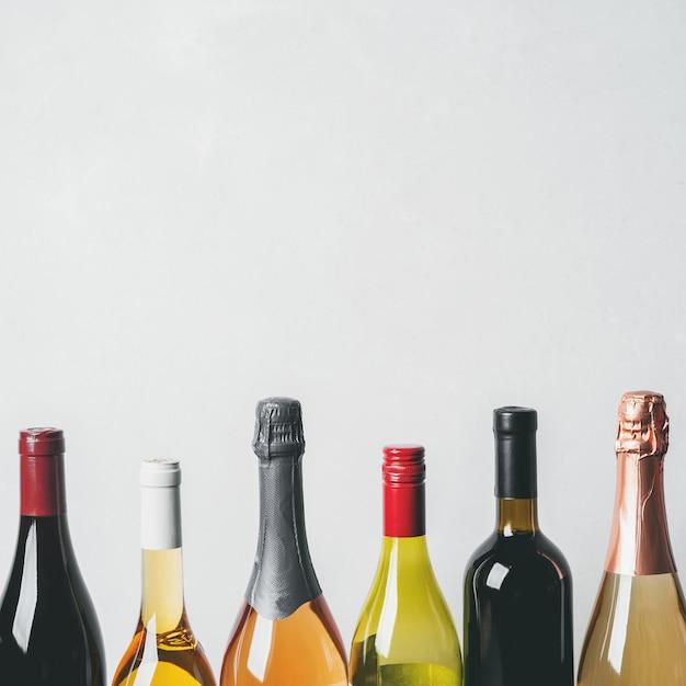 Top di diversi tipi nuove bottiglie di champagne, vino bianco, rosso su sfondo chiaro Foto Premium