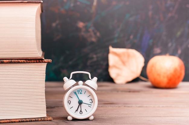 Torna a scuola sfondo con libri, orologio, mela e foglia caduta sulla lavagna Foto Premium
