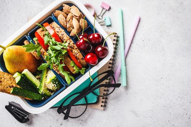 Torna al concetto di scuola con scatola di pranzo con sandwich, frutta, snack, notebook Foto Premium