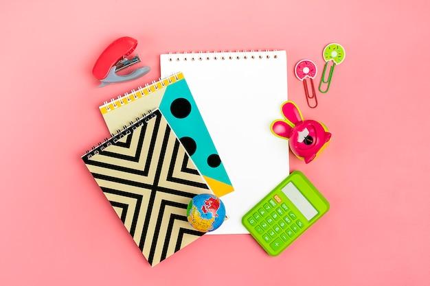 Torna al concetto di scuola. materiale scolastico su rosa, piatto laico. Foto Premium