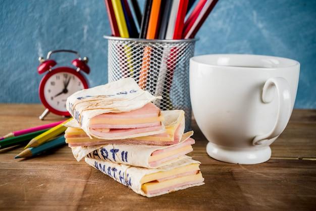 Torna al concetto di scuola, panini scolastici creativi per colazione o pranzo, con formaggio e prosciutto Foto Premium