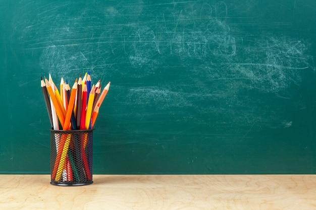 Torna al design del modello di scuola, con materiale scolastico, sfondo della lavagna Foto Premium