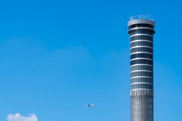 Torre di controllo del traffico aereo in aeroporto con volo aereo di volo internazionale sul cielo blu chiaro. torre di controllo del traffico aeroportuale per il controllo dello spazio aereo tramite radar. tecnologia aeronautica. gestione del volo. Foto Premium