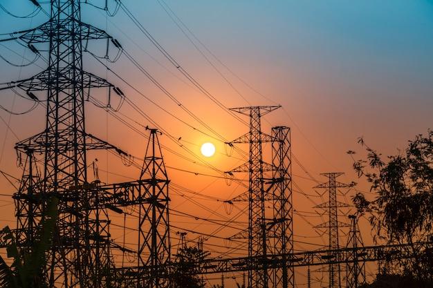 Torre di trasmissione in acciaio ad alta tensione durante il tramonto Foto Premium