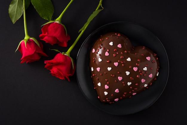 Torta a forma di cuore e rosa rossa per san valentino Foto Premium
