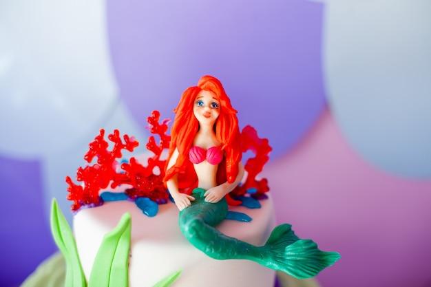 Torta a tema sirena con code di glitter colorati, conchiglie e topper di creature marine Foto Premium
