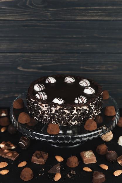 Torta al cioccolato circondata da tartufi al cioccolato e caramelle Foto Gratuite