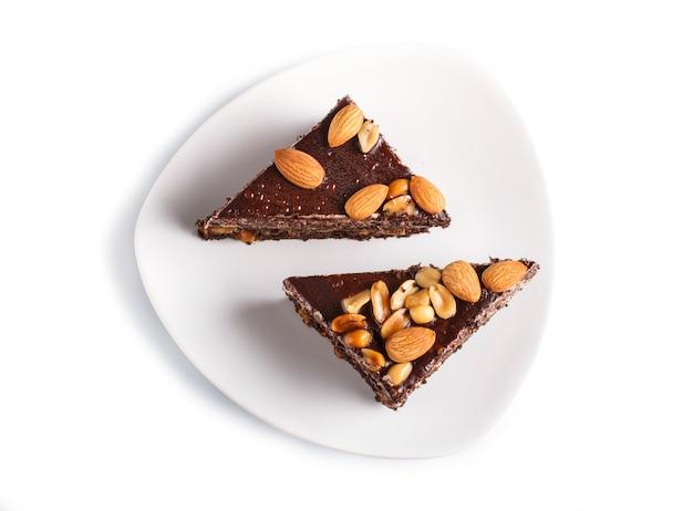 Torta al cioccolato con caramello, arachidi e mandorle isolato su una superficie bianca. Foto Premium