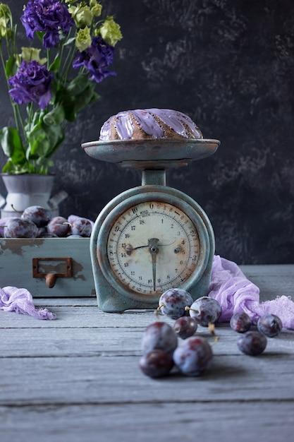 Torta al cioccolato con fiori lilla e prugne in una scatola di legno d'epoca Foto Premium