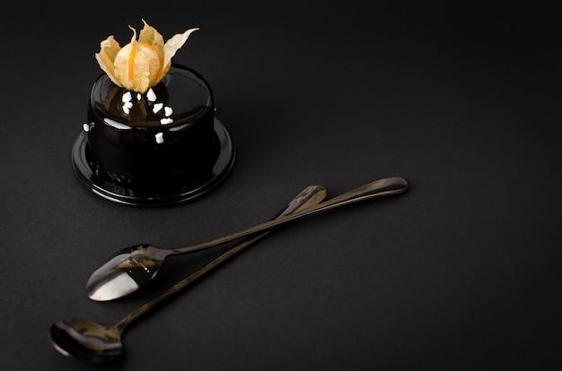 Torta al cioccolato nero condita con glassa di velluto e decorata con physalis su sfondo nero. Foto Premium