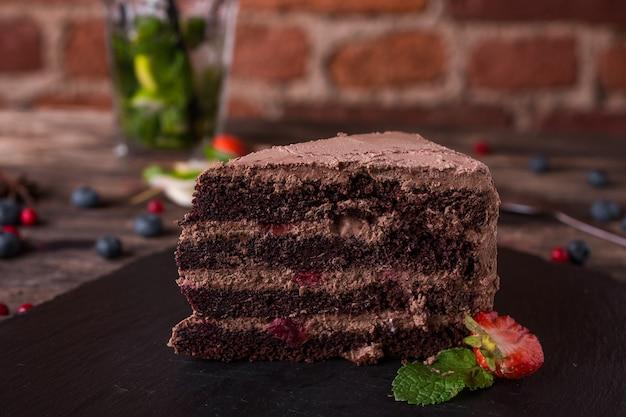 Torta al cioccolato su un piatto di pietra sul tavolo di legno rustico Foto Premium
