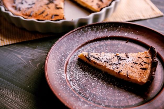 Torta al forno in una forma ceramica cosparsa di fette di cioccolato su un tavolo di legno. Foto Premium