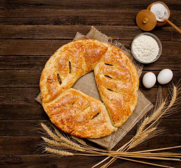 Torta al licenziamento, ingredienti per la cottura, spighe di grano su fondo di legno. Foto Premium