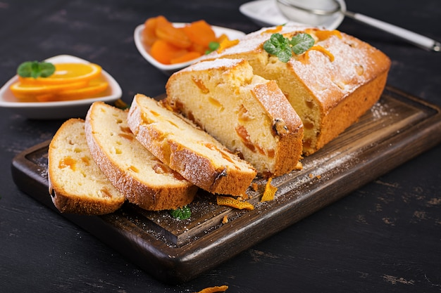 Torta all'arancia con albicocche secche e zucchero a velo Foto Premium
