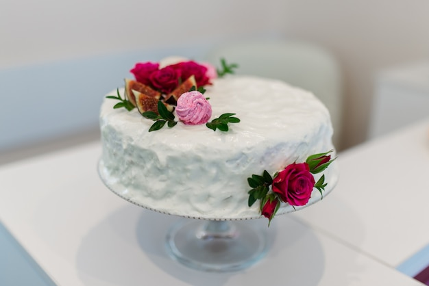Torta bianca con fiori rossi. sfondo bianco Foto Premium