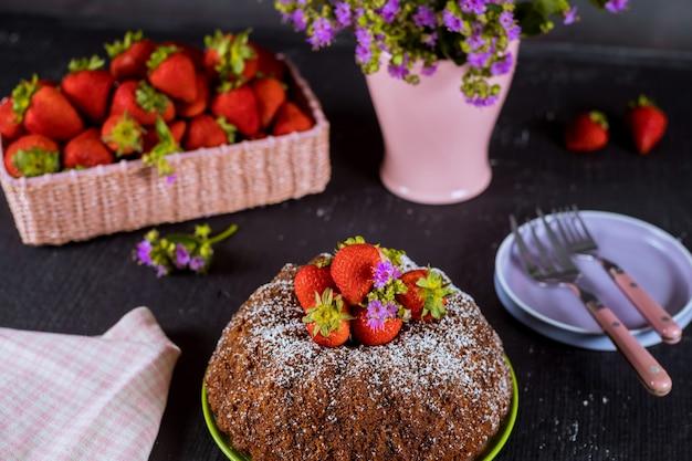 Torta bundt fatta in casa con fragole fresche, piatto, vaso con fiori. Foto Premium