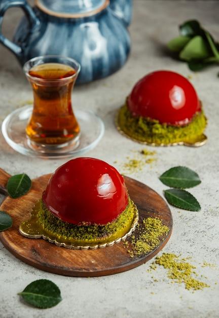 Torta con topping rosso e bicchiere di tè Foto Gratuite