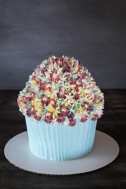 Torta del bigné di compleanno con la decorazione glassata dei fiori sulla tavola di legno rustica. Foto Premium